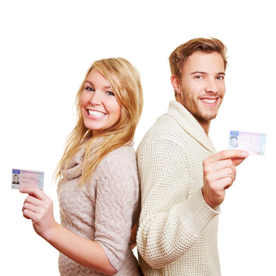 Junges lachendes Paar zeigt zusammen die Fahrerlaubnisse